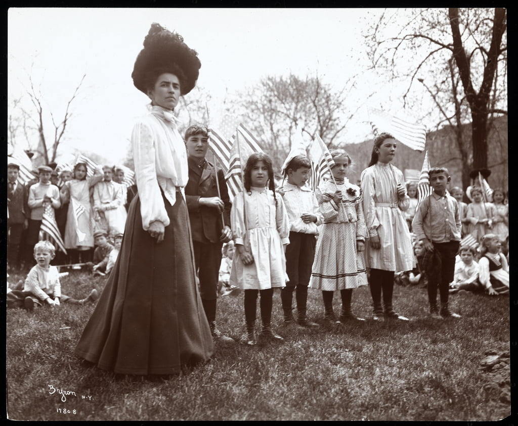 Woman with children holding flags on Arbor Day at Tompkins Square Park, New York, 1904 (silver gelatin print) by Byron Company