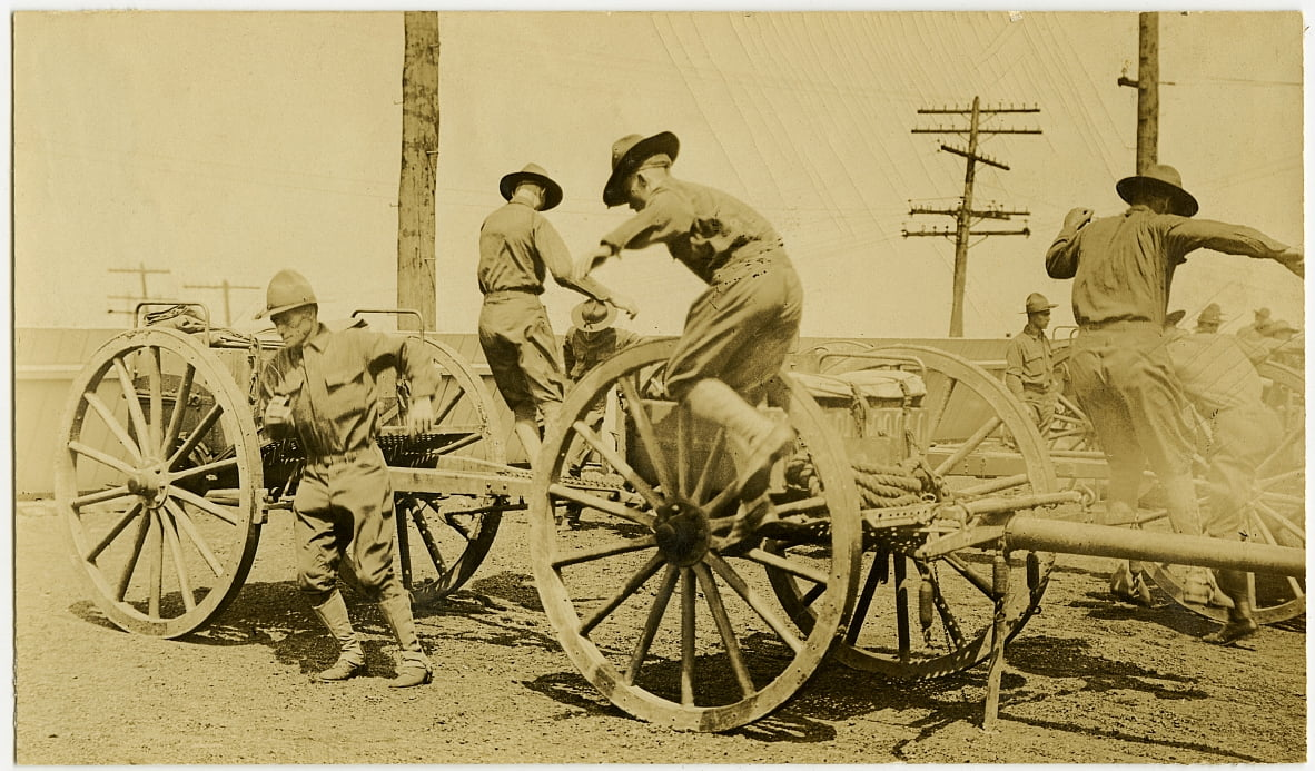Horizontal, sepia photograph showing uniformed men in the process of jumping down from an open cart bearing supplies. Towers of power lines can be seen in the background by Carl Michel
