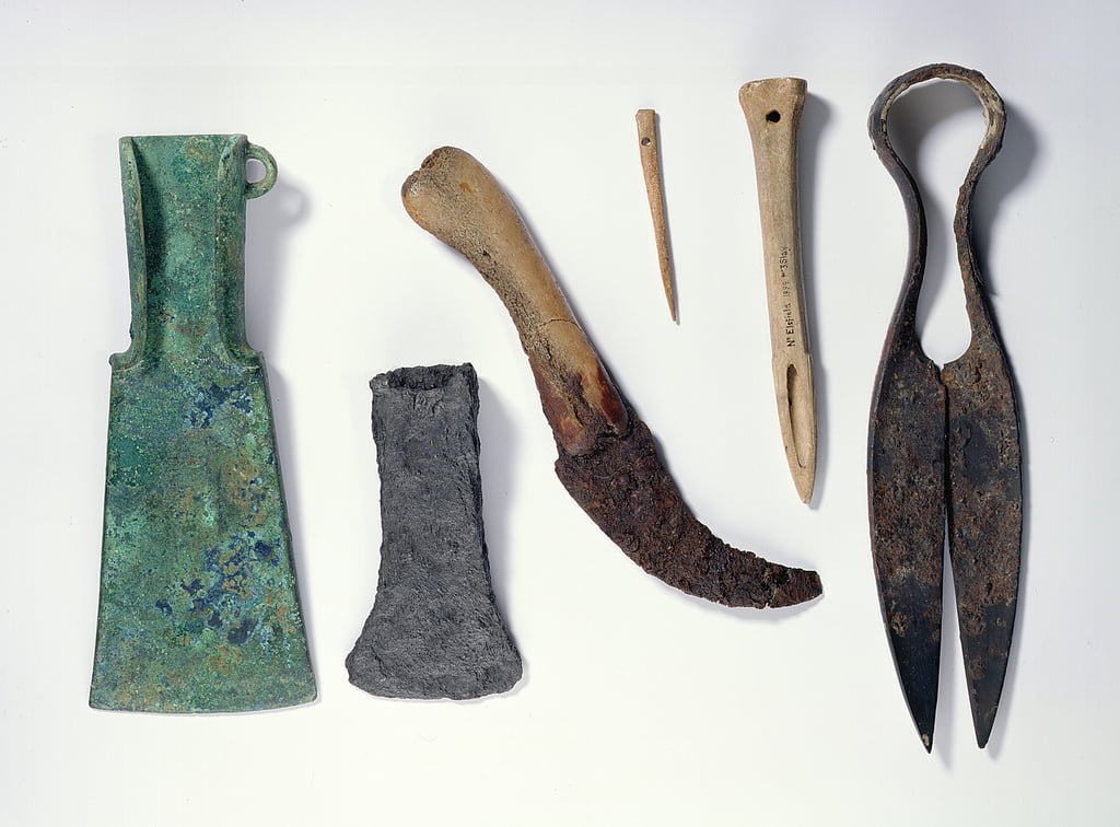 Selection of tools: L-R: early Iron Age bronze axe with bent-over wings; later iron axe; knife with a bone handle; bone needle; bone awl; iron sheers by Iron Age