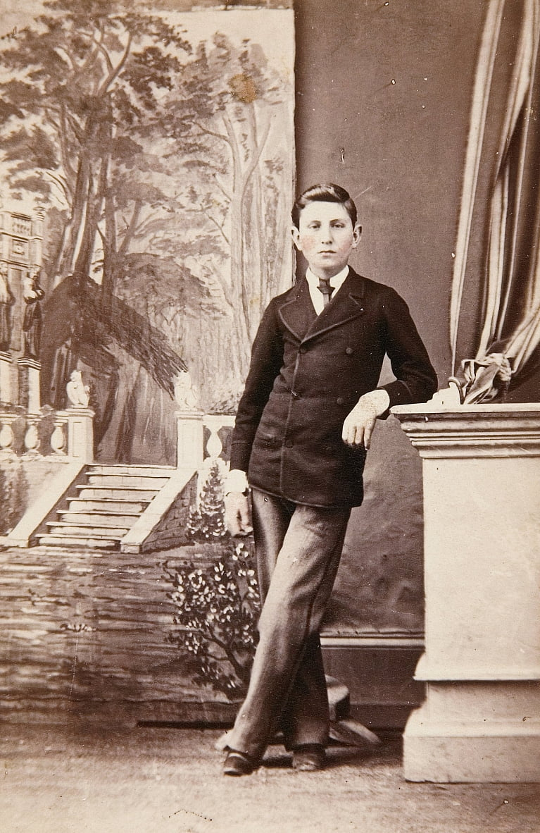 Studio portrait of young man in front of painted background of stairs and garden by William Bentley