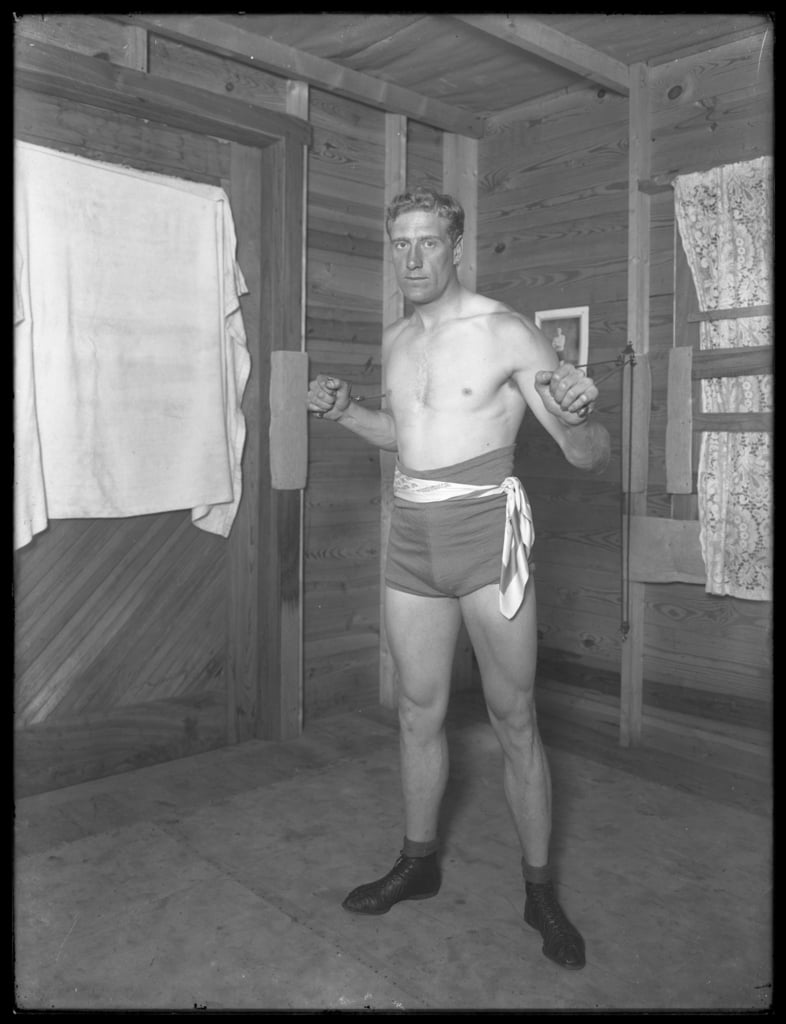 English boxer William Thomas Wells (Bombardier Billy Wells), posing in training togs with weight pulleys, c.1911  by William Davis Hassler